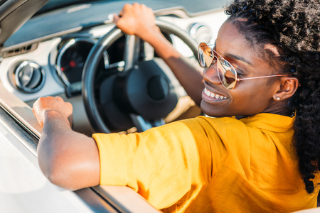 portrait of smiling african american woman in sunglasses riding car Stok Fotoğraf