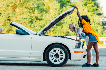 side view of multiethnic women standing near broken car during trip Reklamní fotografie