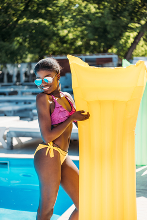 Young beautiful black woman posing with inflatable mattress at poolside at resort