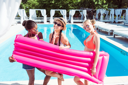 Happy multiethnic women posing with inflatable mattress near swimming pool at resort