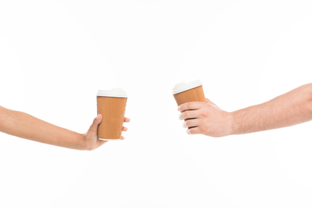 Close-up cropped view of two human hands holding disposable cups, isolated on white