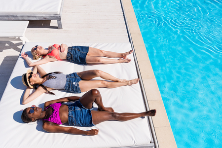 Young beautiful multiethnic women lying and resting at poolside at resort