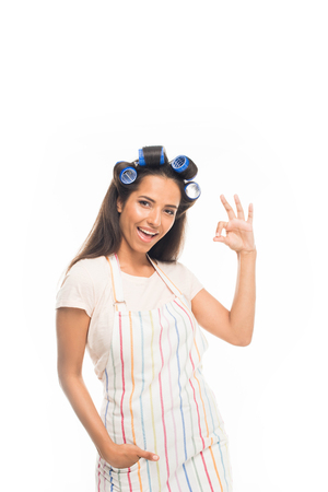 Young housewife with curlers showing ok sign, isolated on white