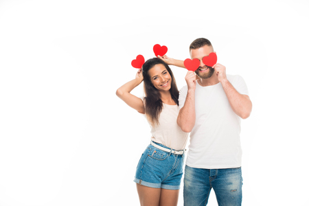 portrait of attractive young couple standing with red paper hearts, isolated on white Stock Photo