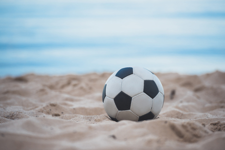 close up view of soccer ball on summer sandy beach