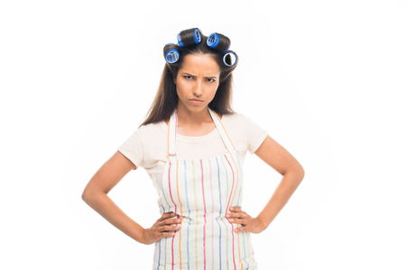 Angry housewife with curlers standing with hands on hips, isolated on white