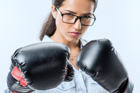portrait of serious businesswoman in boxer gloves looking  at camera isolated on blue 写真素材 - 102365966