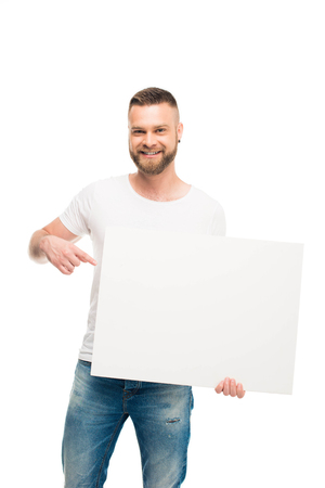Handsome bearded man holding blank banner and pointing on it, isolated on white