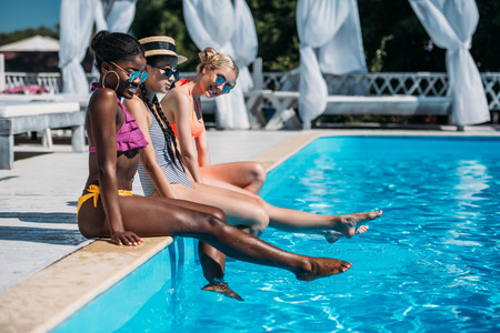 Young beautiful multiethnic women sitting near swimming pool at resort Stok Fotoğraf