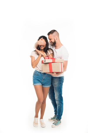 'portrait of young attractive man surprising his girlfriend by gifts, isolated on white