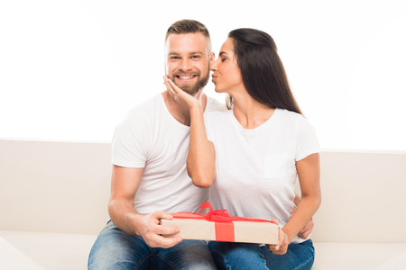 portrait of young attractive couple with gift box, isolated on white