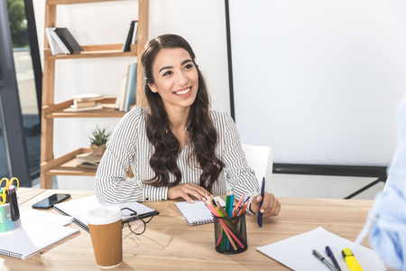 portrait of smiling asian businesswoman sitting at workplace with various office supplies