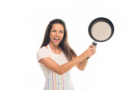 Yelling housewife in apron, standing with frying pan in hands , isolated on white
