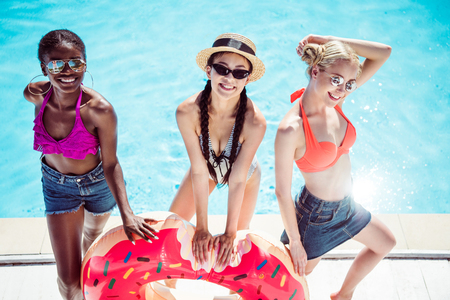 Happy multiethnic women posing with inflatable donut near swimming pool at resort