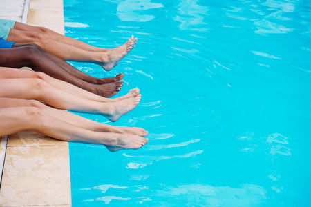 Young people lying near swimming pool. Cropped image of legs over blue water Stok Fotoğraf