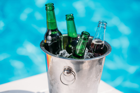 Close-up view of Ice bucket with beer standing next to swimming pool