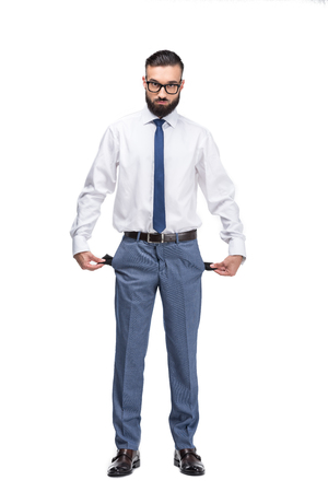 handsome poor businessman with empty pockets, isolated on white  写真素材