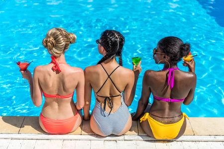 Young beautiful multiethnic women with cocktails sitting near swimming pool at resort