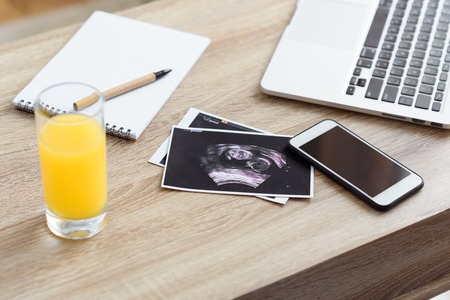glass of juice, ultrasound scan of unborn baby and digital devices on wooden tabletop