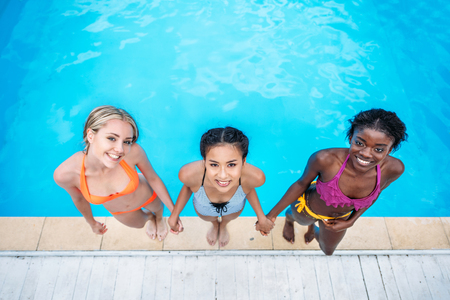 Young beautiful multiethnic women standing near swimming pool at resort