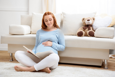 beautiful redhead pregnant woman reading book at home Stock fotó