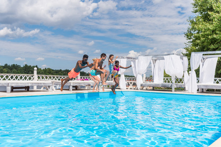 Group of beautiful young multiethnic people looking happy while jumping into the swimming pool together Stok Fotoğraf - 102366301