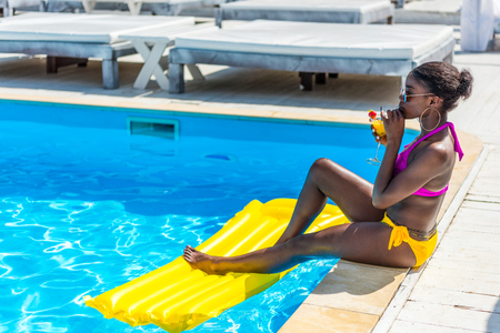 African american woman resting with cocktail near swimming pool at resort