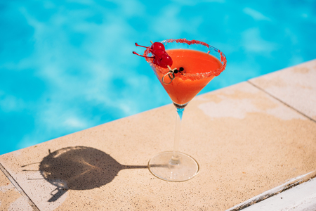 Colorful tropical cocktail with berries on edge of swimming pool