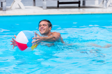 Young happy caucasian man playing with ball in swimming pool