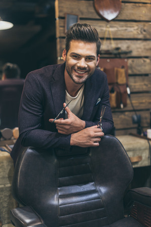 Portrait of handsome caucasian male barber with fashionable hairstyle at barber shop