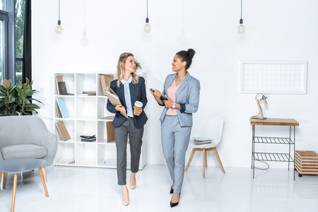 multicultural businesswomen having conversation while walking in office