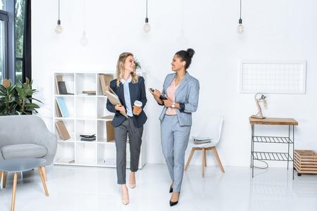 Empresarias multiculturales conversando mientras camina en la oficina Foto de archivo