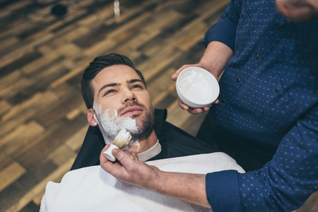 Barber applying foam before shaving of customer in barber shop