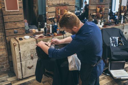 Barber shaving customers beard in vintage barber shop