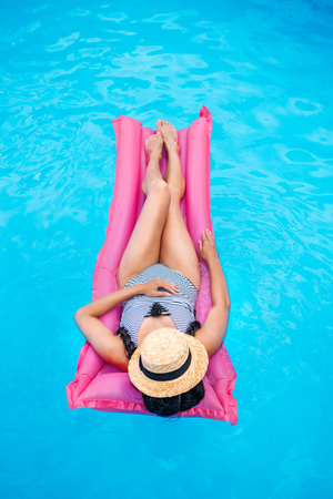Young woman with straw hat covering face floating on air mattress in swimming pool