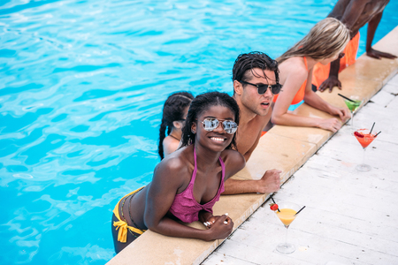 Group of young happy multiethnic people with cocktails in swimming pool