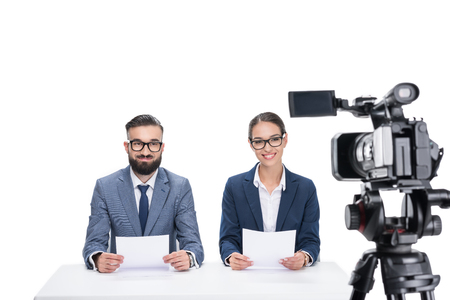 two smiling newscasters with papers sitting in front of camera, isolated on white  写真素材