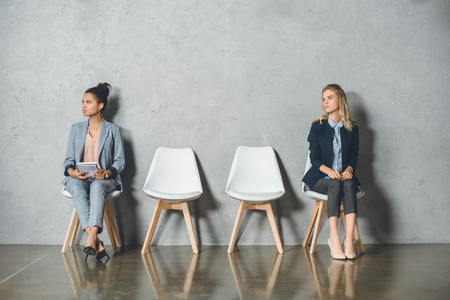 young multicultural businesswomen sitting on chairs and waiting for job interview Imagens