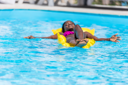 African american woman floating on inflatable mattress in swimming pool