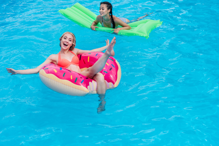 Young multiethnic women floating on inflatable mattresses in swimming pool at resort