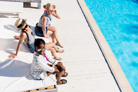 Young beautiful multiethnic women sitting at poolside at resort  Stok Fotoğraf