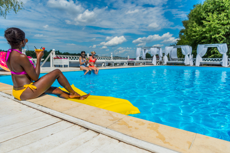 Young beautiful multiethnic women sitting near swimming pool at resort Stok Fotoğraf