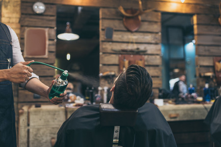 Cropped image of barber applying perfumes to customer at barber shop