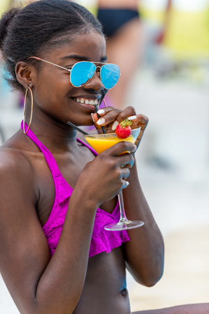 African american woman in pink swimwear with tropical cocktail at resort Stok Fotoğraf