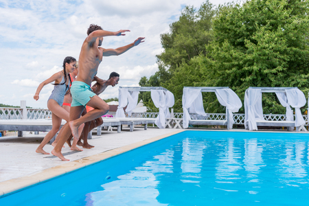 Group of beautiful young multiethnic people looking happy while jumping into the swimming pool together Stok Fotoğraf