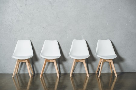 white empty chairs for job interview standing in line in hall