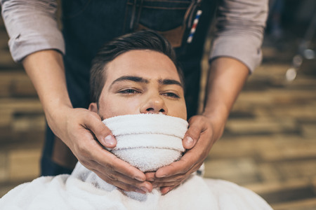 Client with hot towel on face before shaving in barber shop Stock Photo