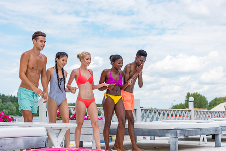 Happy multiethnic friends standing ready to jump into swimming pool