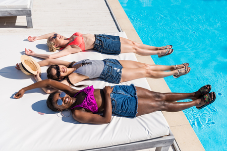 Young beautiful multiethnic women lying and resting at poolside at resort Stock Photo - 102358296