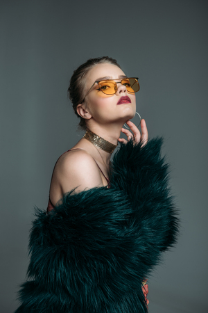 young seductive attractive woman posing in green fur coat and orange sunglasses for fashion shoot, isolated on grey